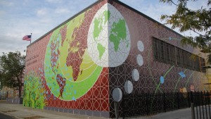 As Ben Volta's Micro to Macro mural wraps around Morton McMichael school, wraps around the corner and moves north, the imagery becomes cosmic with solar systems and planetary orbits. (Emma Lee/WHYY)  Courtesy of Newsworks.org