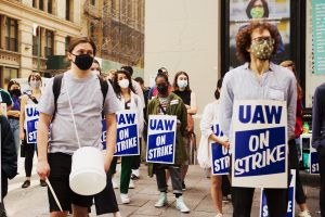 students in masks, social distancing, wearing signs saying UAW on strike