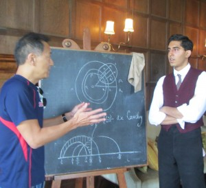 Ken Ono (left) explains some mathematics to Dev Patel(right), before shooting a scene.